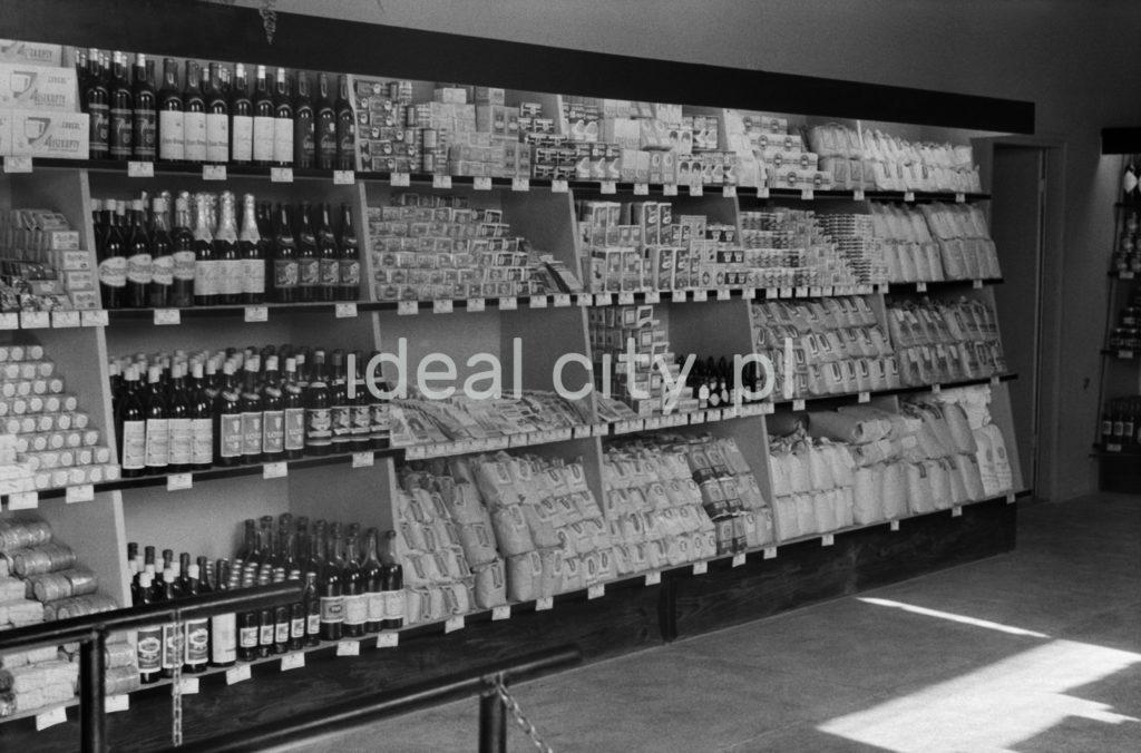 Widok na wypełnione towarami półki sklepowe.
