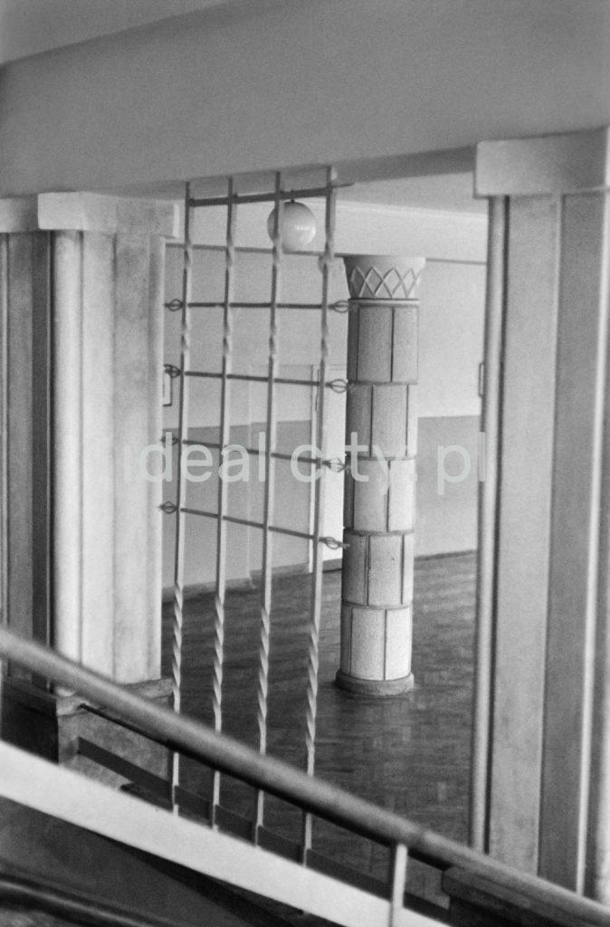 Widok przez kratę na pokryty ceramiką filar konstrukcyjny pośrodku szkolnego korytarza.
