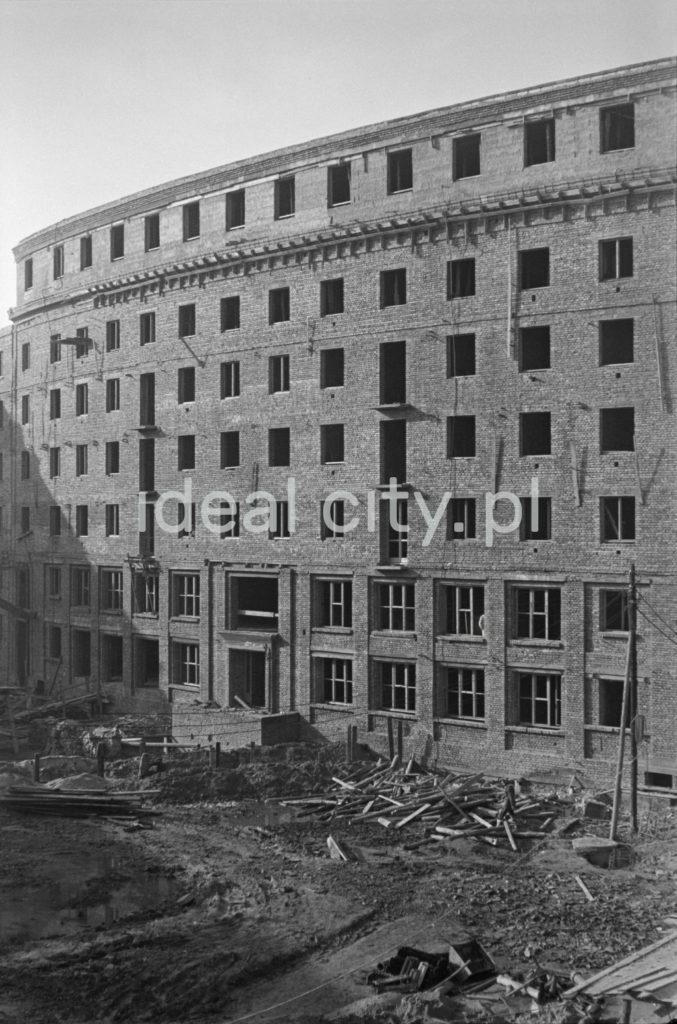 Widok na nieotynkowaną elewację półokrągłego, siedmiokondygnacyjnego budynku mieszkalnego z cegły.