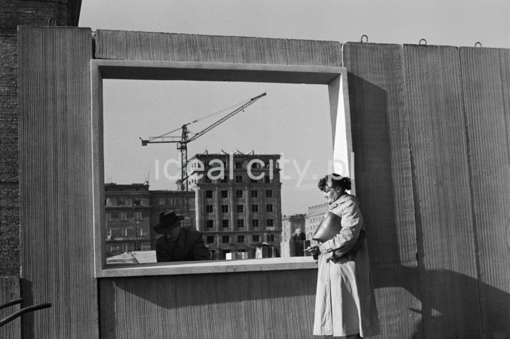 Kobieta w płaszczu, z teczką pod pachą, ogląda wraz z mężczyzną w kapeluszu prefabrykowaną ścianę budynku z gotowym otworem okiennym, w tle bloki mieszkalne.