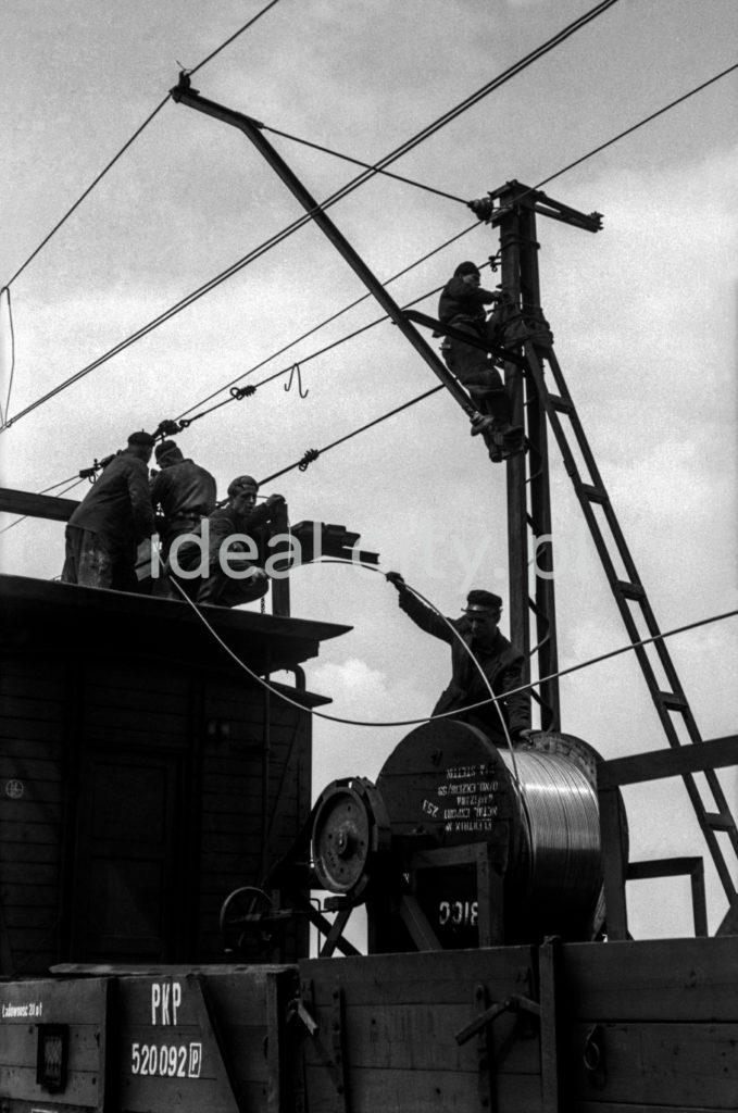 Ekipa montuje sieć trakcyjną przy torach kolejowych.