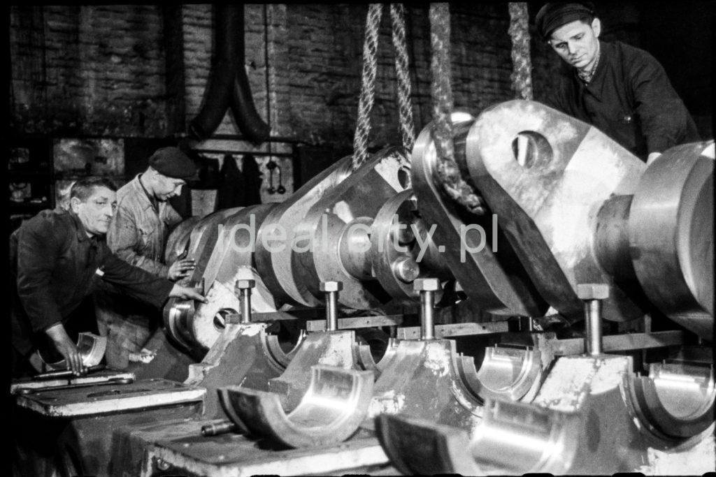 Pracownicy wykonują prace przy potężnym wale korbowym.