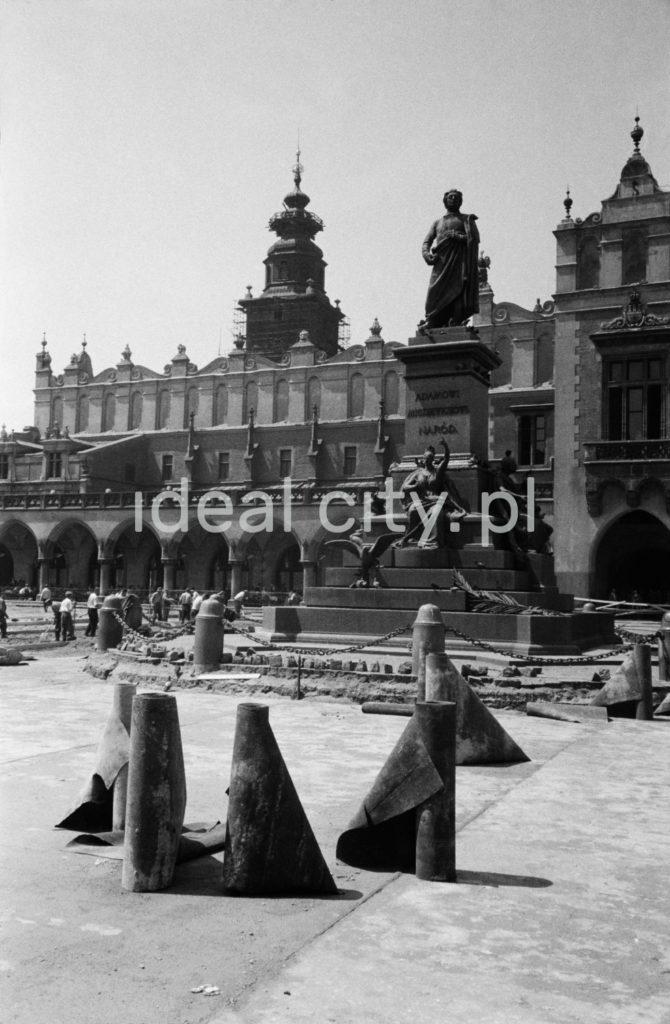 Rolki z papą czekają na płycie Rynku Głównego na rozłożenie. W tle pomnik Adama Mickiewicza,Sukiennice, Wieża Ratuszowa.