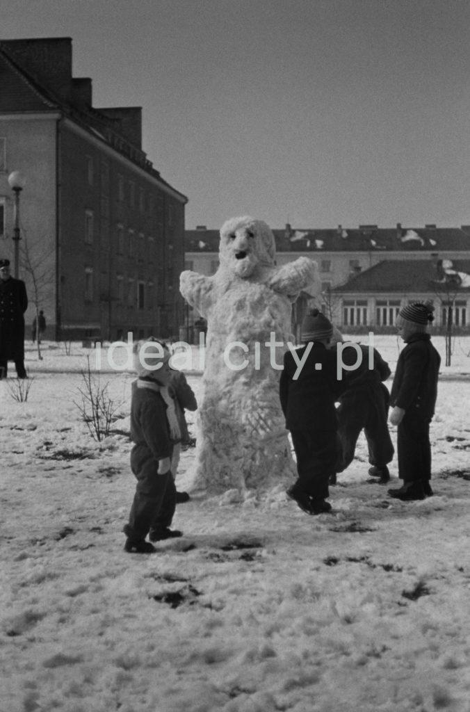 Dzieci lepiące bałwana na zaśnieżonym placu pomiędzy blokami mieszkalnymi.