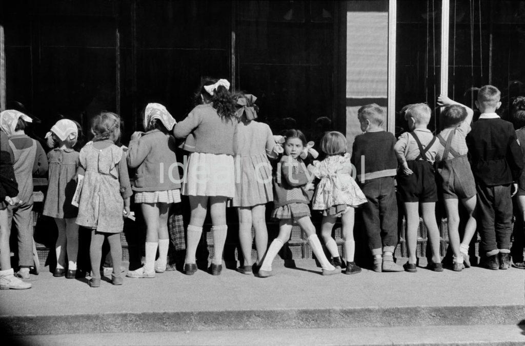 Grupa dzieci i dorosłych zagląda przez witrybę do wnętrza sklepu.