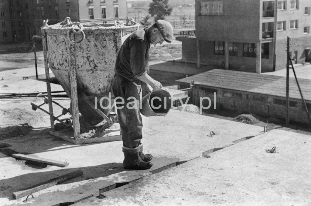 Robotnik na otwartej kondygnacji nowo budowanego budynku pracuje nad łączeniem prefabrykowanych płyt. W tle bloki.
