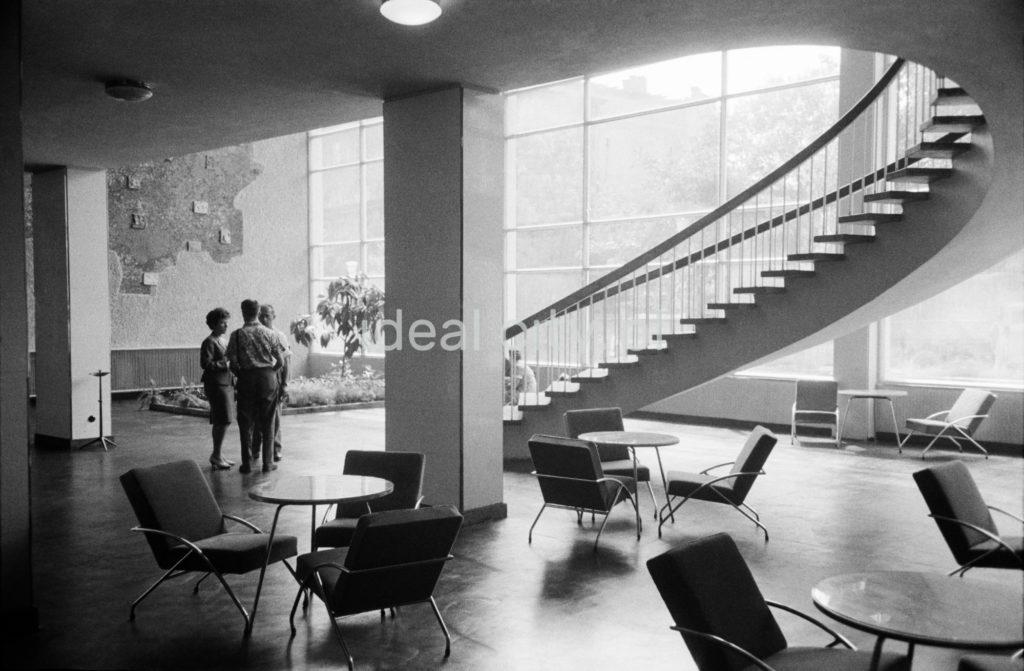 Ujęcie na parter hotelowego lobby, z którego do góru prowadzą spiralne schody.
