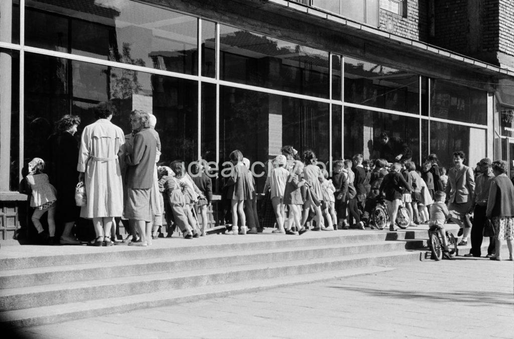 Grupa dzieci jak również dorosłych zagląda przez szybę do pawilonu sklepowego.