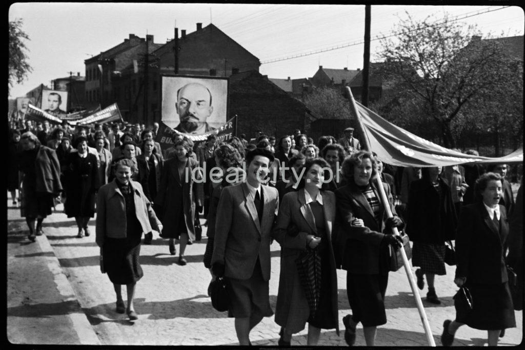 Ubrani odświętnie ludzie maszerują w pochodzie niosąc transparenty i portret Lenina.