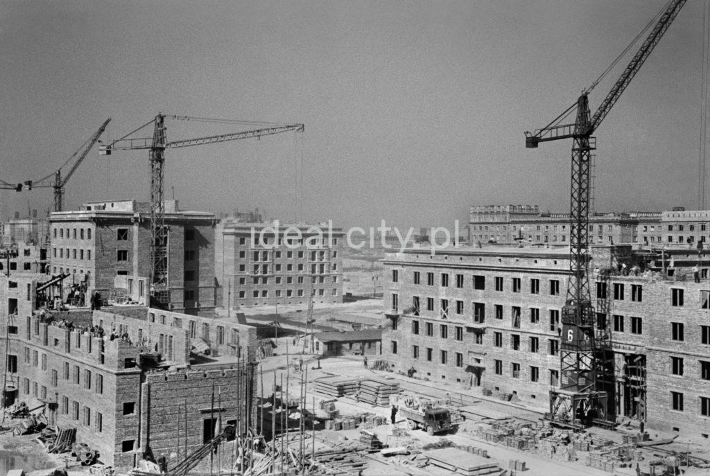 Widok z wysokości na szereg, zlokalizowanych obok siebie placów budowy, widoczne nieukończone kilkupiętrowe budynki z cegły oraz wysokie żurawie.