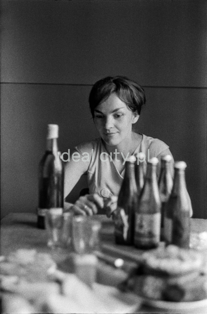 Skonsternowana kobieta siedzi przy stole zapełnionym butelkami.