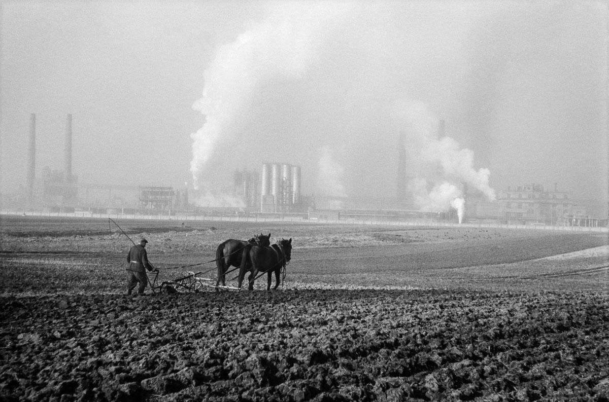 Rolnik orze pole uprawne za pomocą pługa zaprzągniętego w konia, w tle dymiące kominy kombinatu.