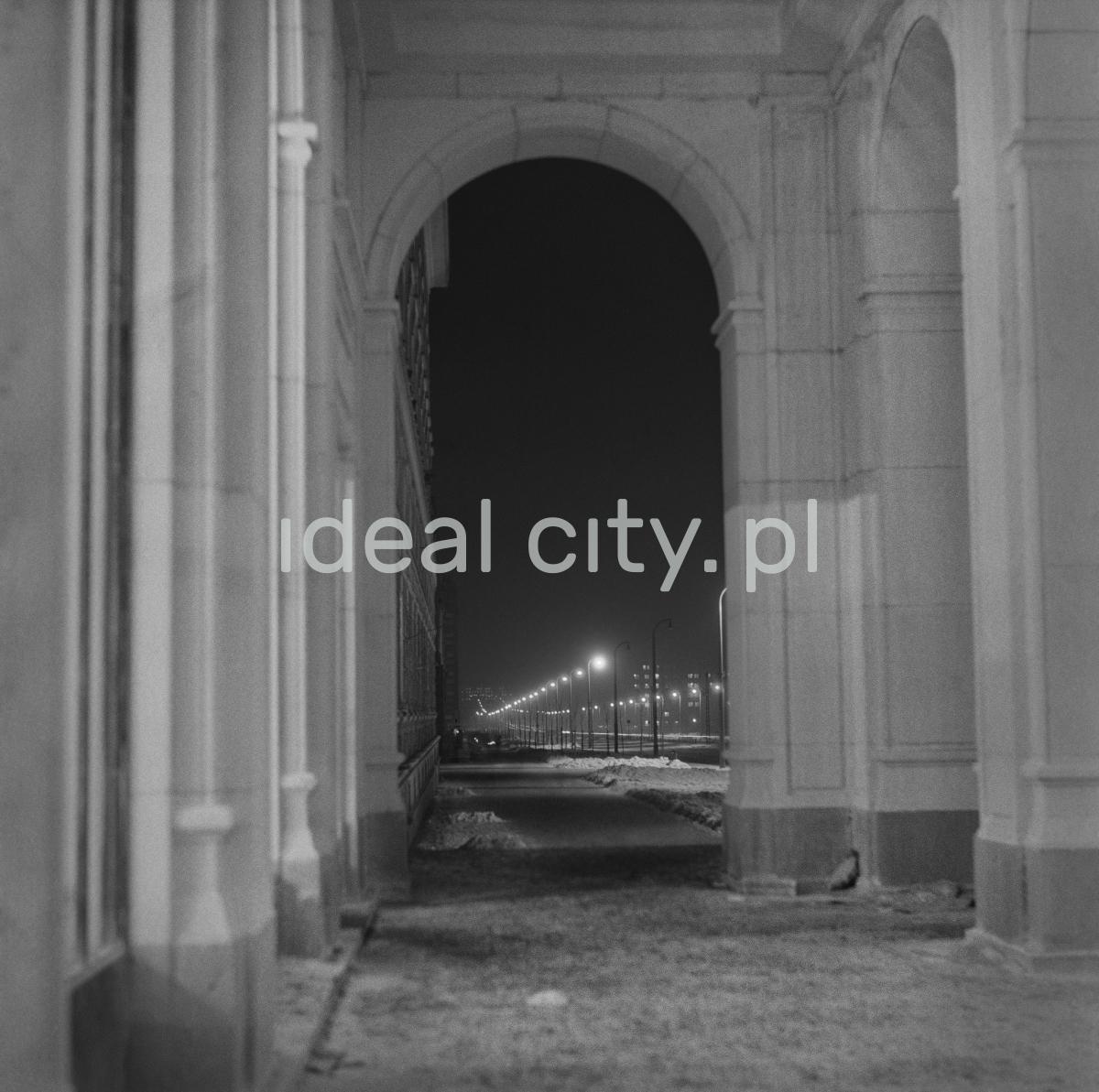 Nocna perspektywa oświetlonej ulicy, ujęcie spod arkad budynku mieszkalnego.