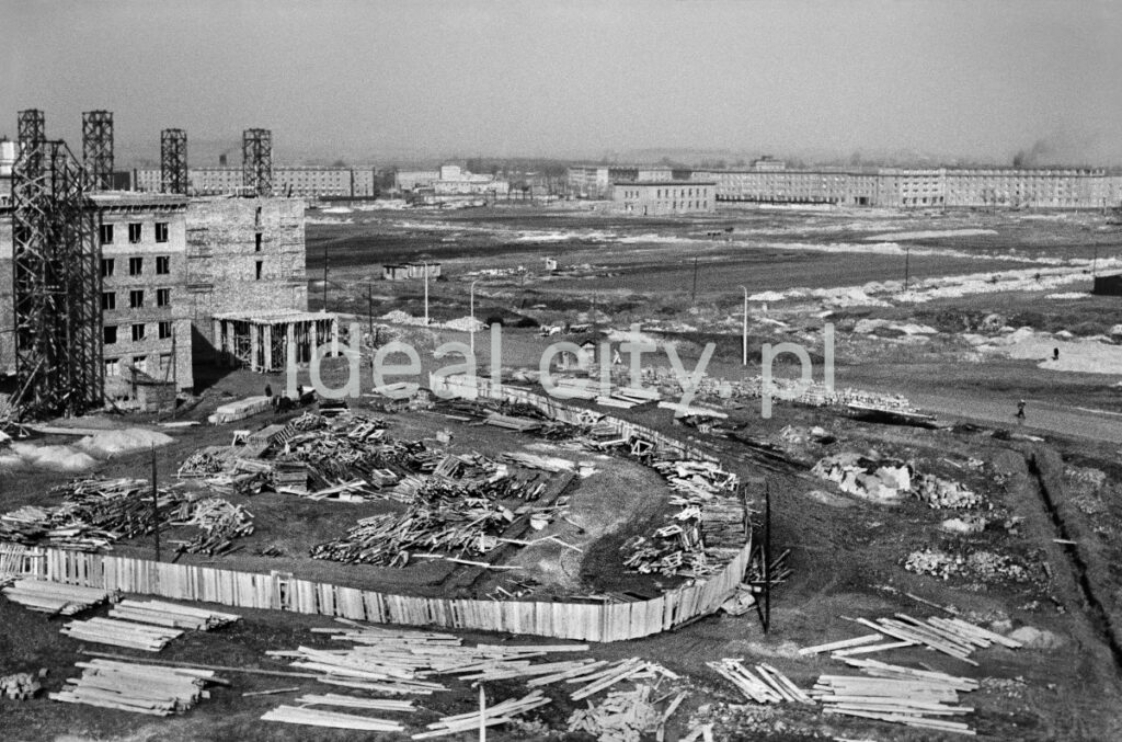A view of the construction site from above, in the foreground a wooden fence fenced in. Chaos on both sides.