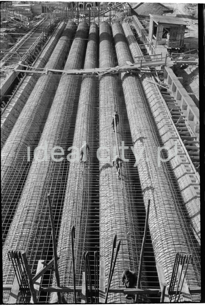 A view from above on the huge pipes covered with reinforcements lying next to each other on the ground.