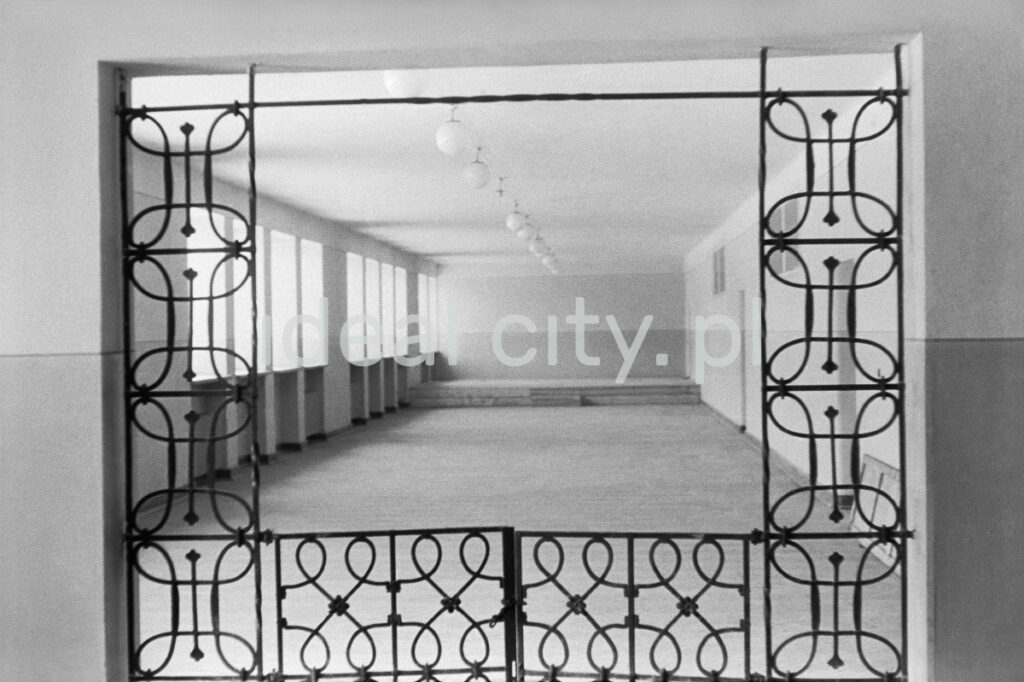 A view through the tilted iron grille onto the school corridor.
