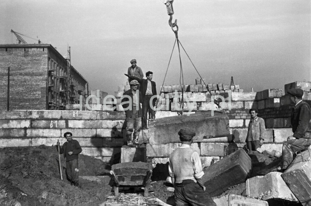 A team of workers is waiting for a prefabricated element fed by a crane.
