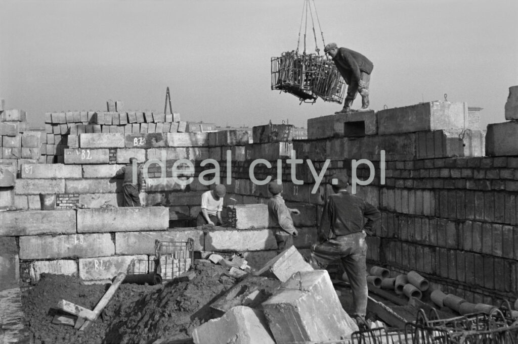 Workers assemble the walls of the building from massive concrete blocks.