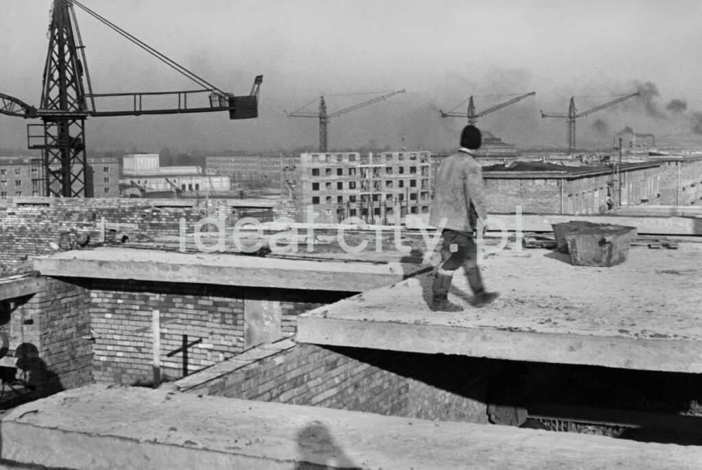 A laborer walks on the storey under construction, other buildings and construction cranes in the background.
