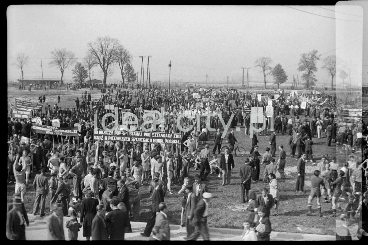The crowd gathered on the meadow with banners prepares for the march.