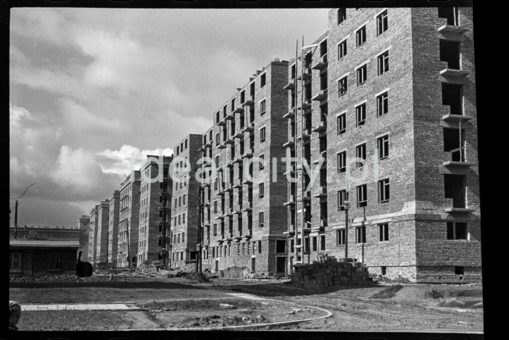 The shot shows a newly completed brick apartment block in a rough state.