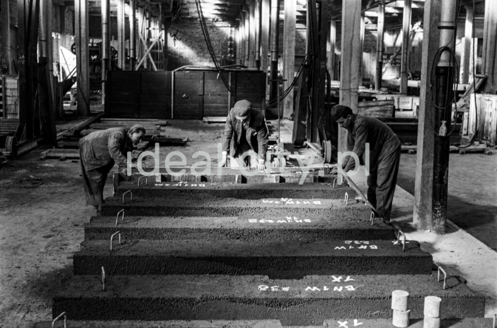 Workers place newly poured prefabricated concrete blocks in the production hall.