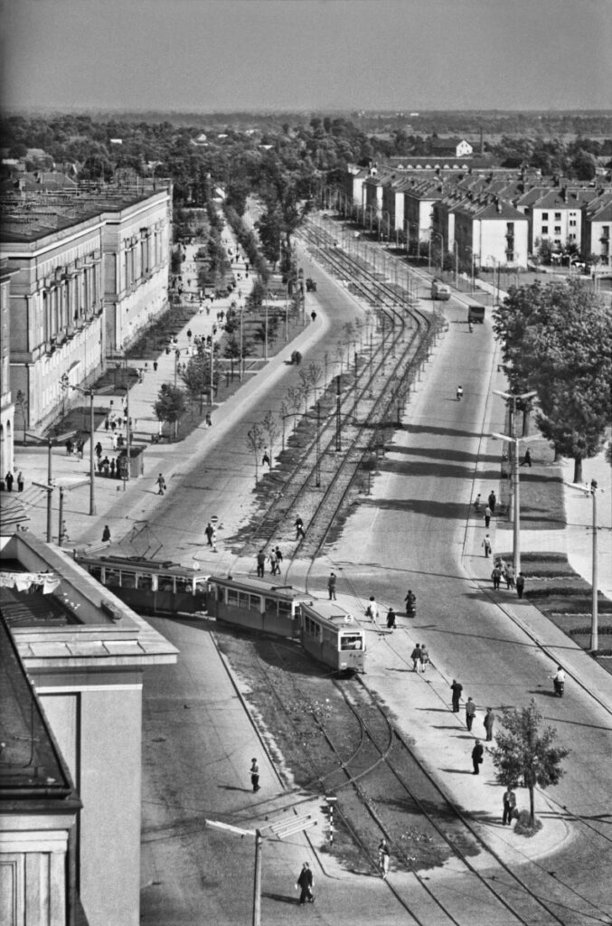 A view from above on a wide avenue with a tram track in the middle.