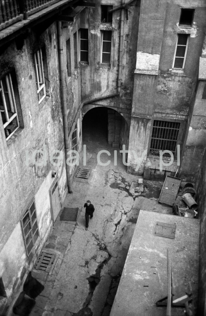 A view from the window on the backyard of an old, neglected tenement house, which is dynamically entered by a man.
