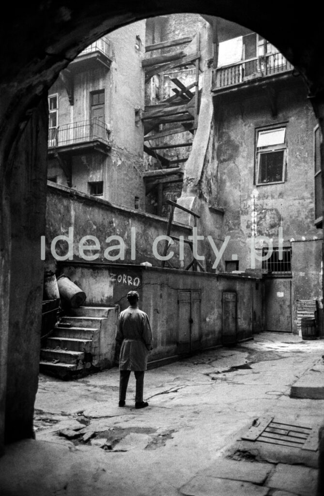 The man in the coat looks up the run-down yard of an old tenement house.