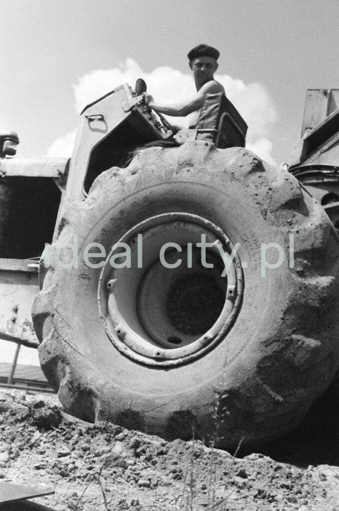 A man on a tractor, shot from below - a massive tire in the foreground.
