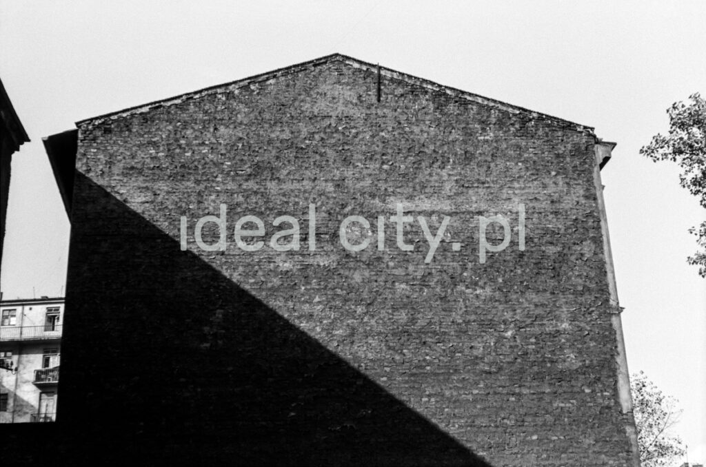 A view of the brick wall of the building, cut across by the shadow from the neighboring building.