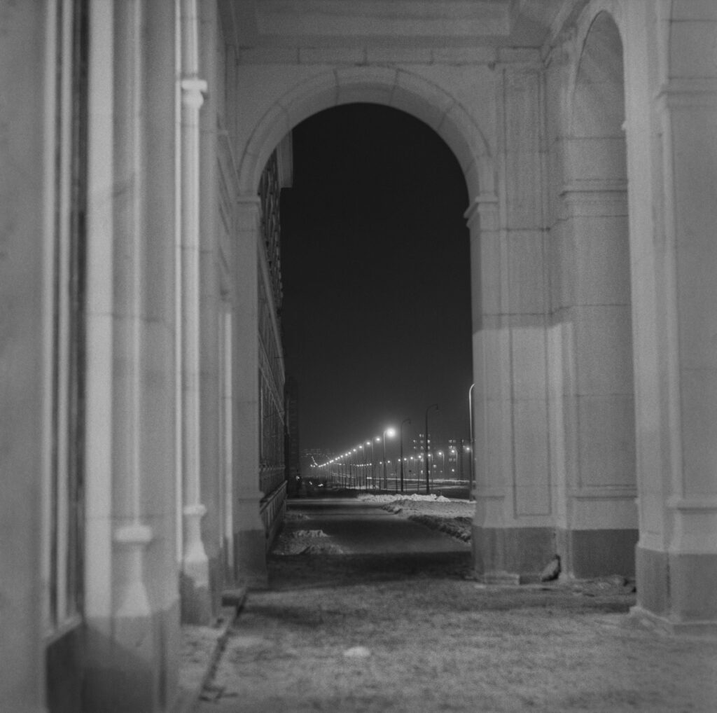 Night perspective of the illuminated street, shot from under the colonnade.