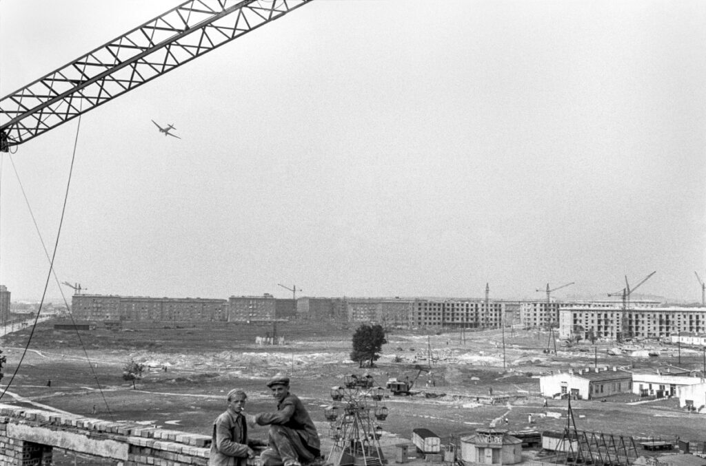 A wide perspective from a height over the city under construction, in the foreground two little figures of workers, an airplane in the sky.