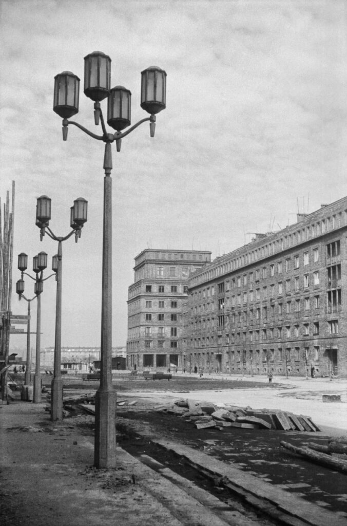 View of the representative city square under construction. Monumental lanterns in the foreground, residential buildings in the background.