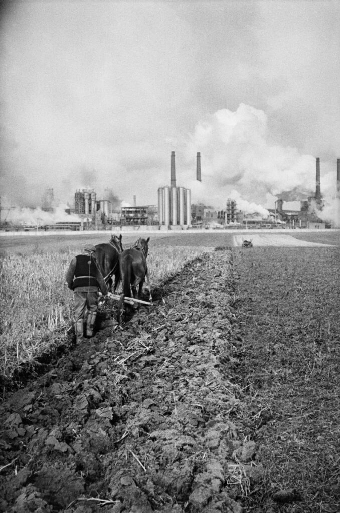 A farmer plows a field with a horse-drawn plow, in the background the smoking chimneys of the plant.