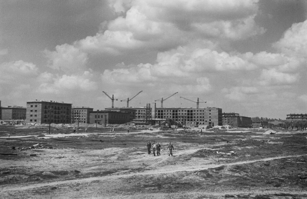 A view of the construction site, residential buildings in the background, in the center of the frame, a few small figures walk forward.