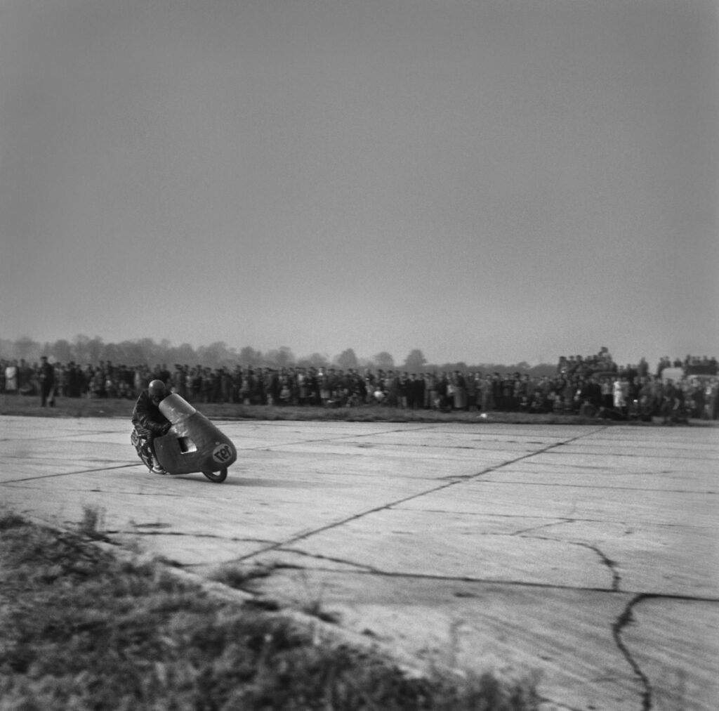 The motorcyclist is driving the bend at high speed, with spectators in the background.