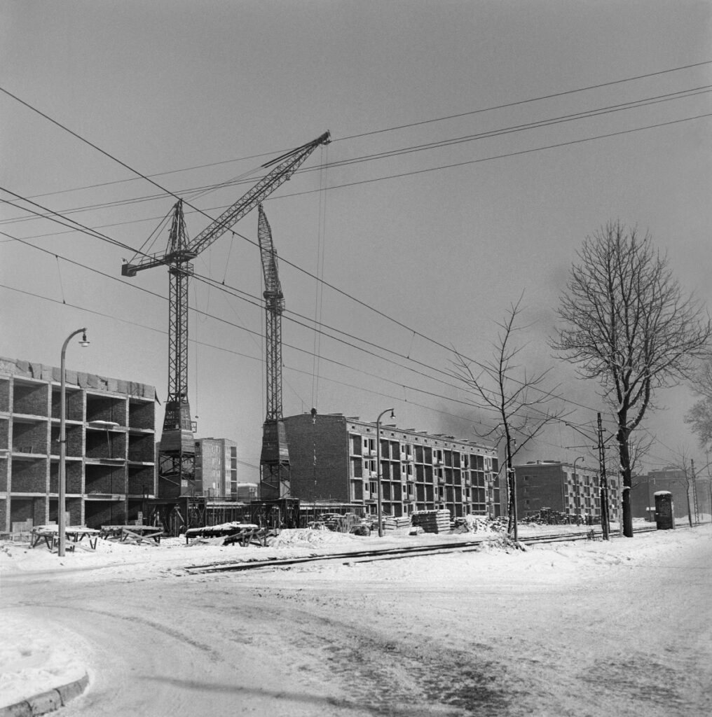 Construction of low blocks along the tram line. Old type construction cranes in the foreground. Winter shot.