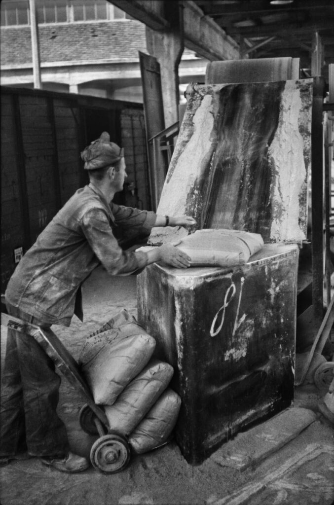 The worker throws large sacks onto the conveyor belt.