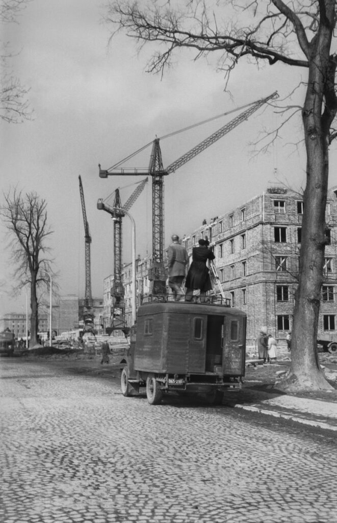 Two men with a tripod and a camera, standing on the roof of a transport car, film residential buildings along the tram line.
