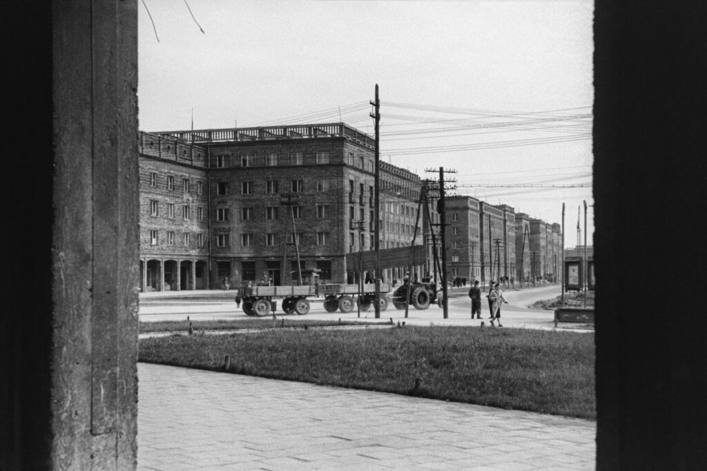 A view of a low, compact block of brick buildings, a tractor with trailers passing in the center of the frame, people walking by.