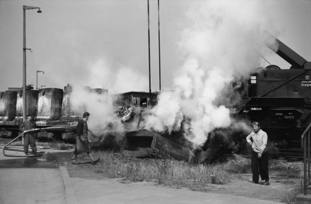 Steam puffs from extinguished water from the jets of objects lying next to the railway depot, near three men, one of them smokes a cigarette.