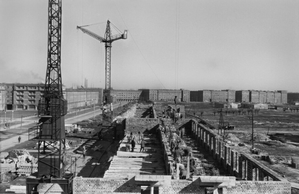 A perspective view from a height for the construction of the foundations of a residential block, completed residential buildings on the horizon.