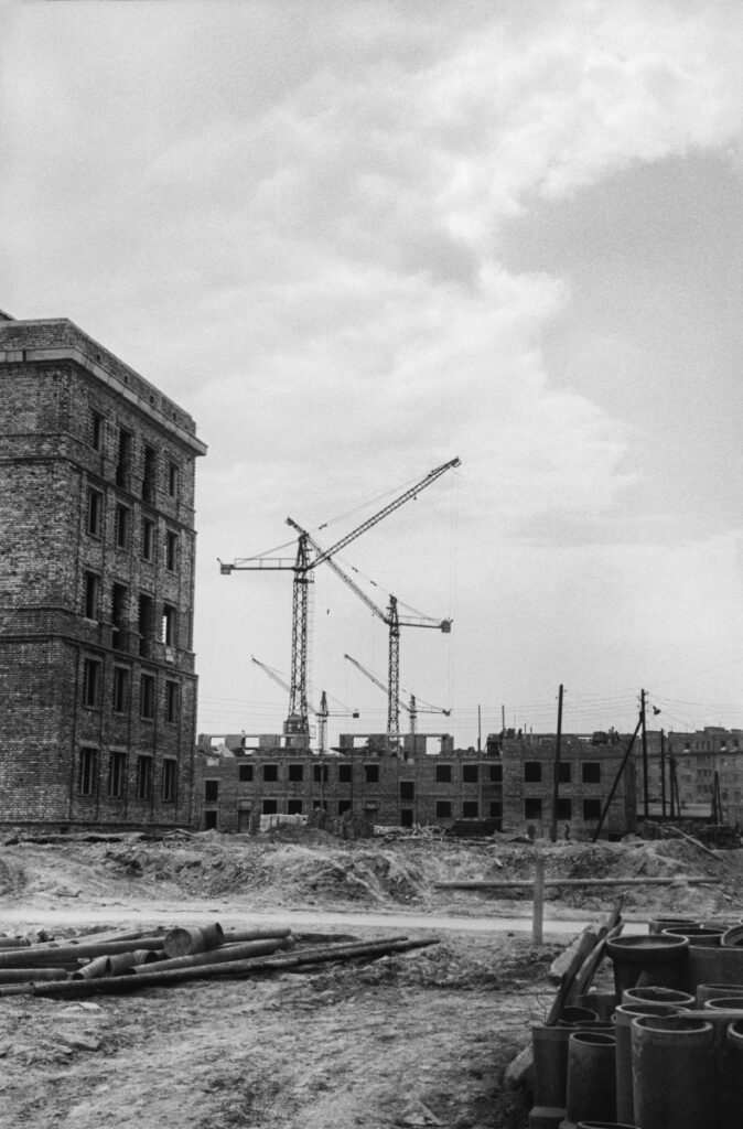A view of the construction site, on the left, the building is closed, in perspective, the cranes and the construction of the first floors of subsequent blocks.