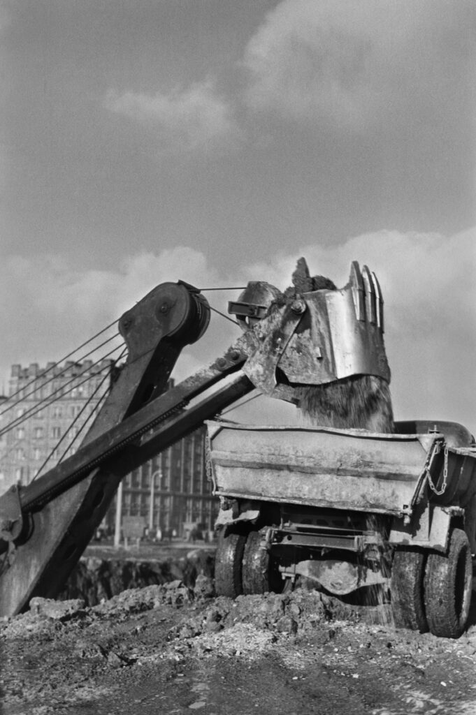 The excavator loads soil from the excavation onto a truck semi-trailer, residential buildings in the background.