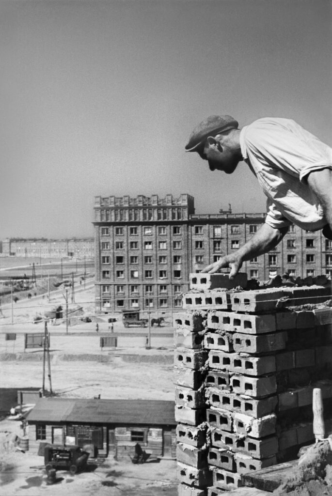 A bricklayer in a white shirt and flat cap places the bricks of the building on the upper storey, with a completed block in perspective.