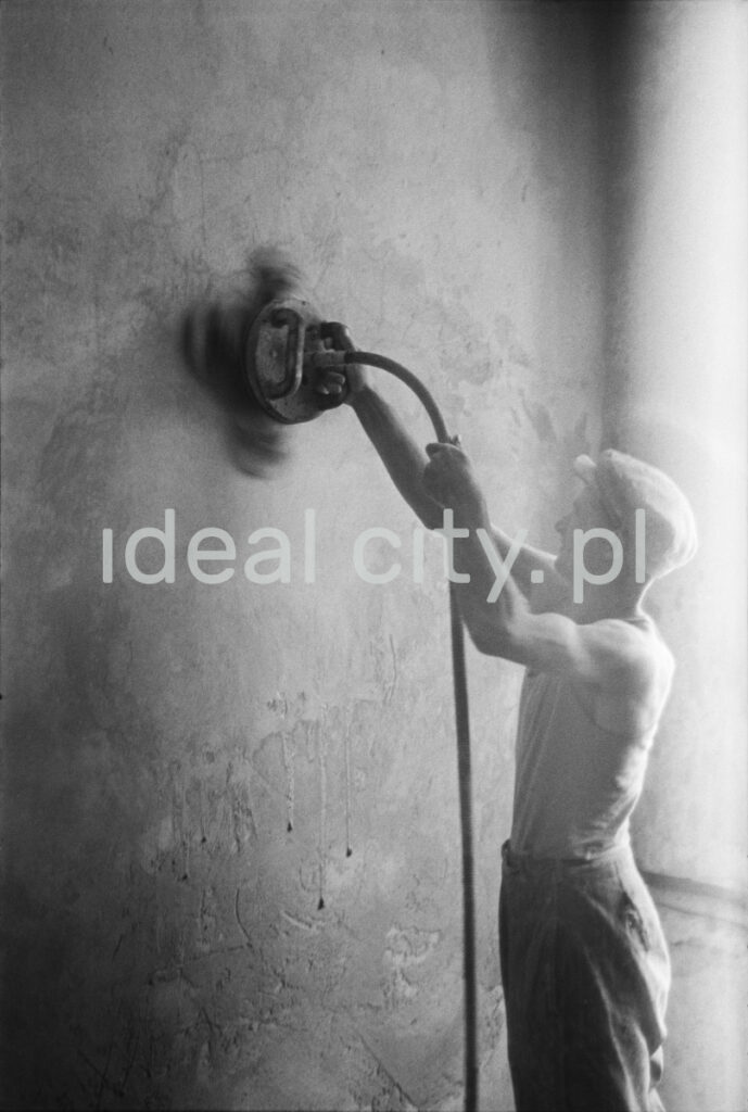 A worker in a tank top and a flat cap polishes the wall with an automatic grinder.