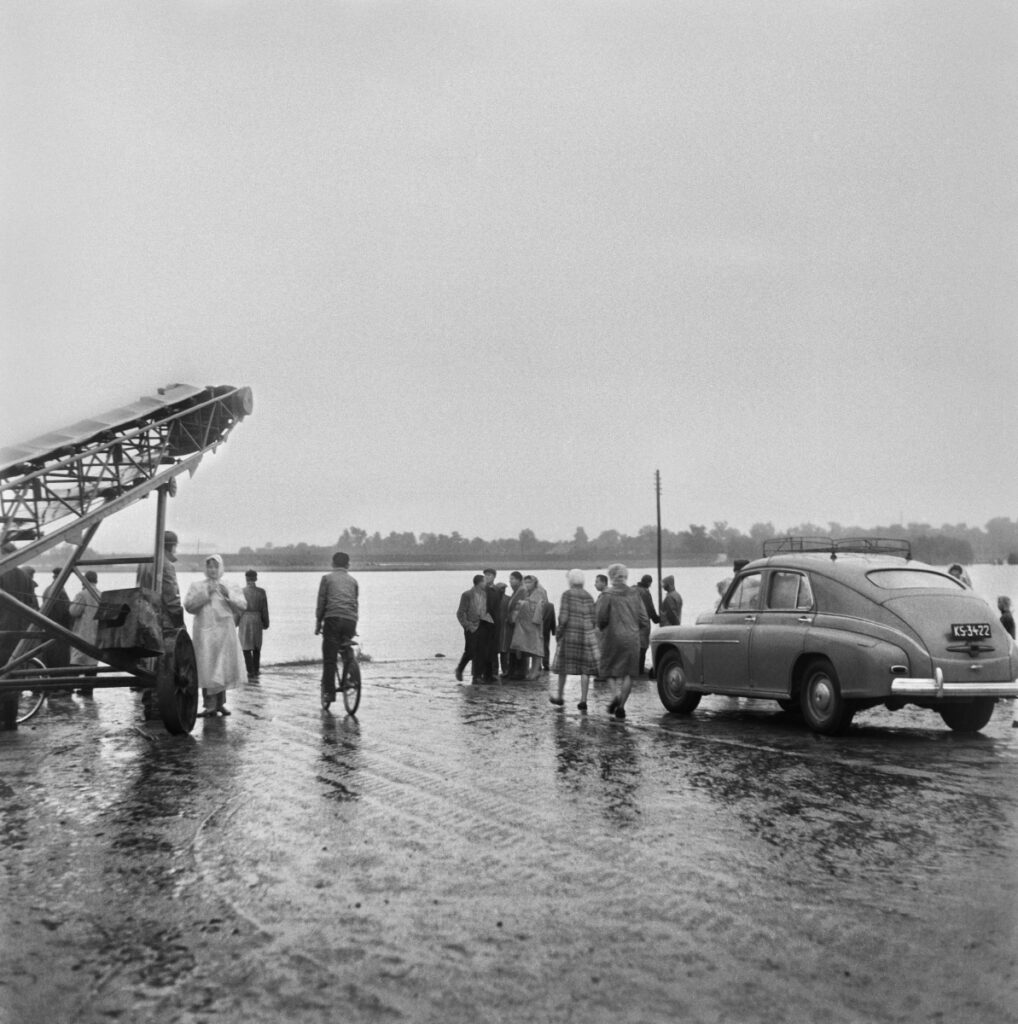 Onlookers gathered on the road that runs along the river bank. On the right, a parked car.