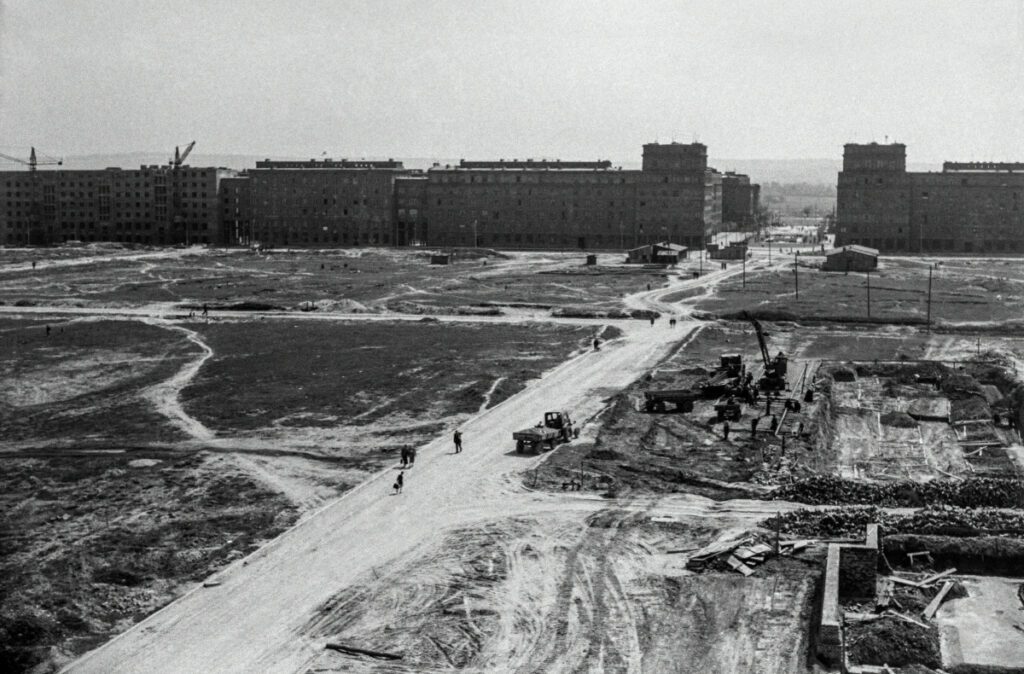 View of the construction site from a height, monumental residential buildings completed in the background.