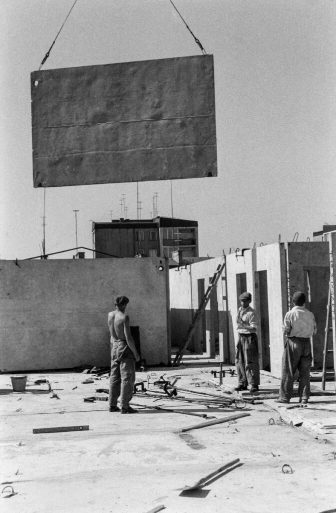 Workers are placing a prefabricated slab on the building's storey, which is fed to them by a crane.